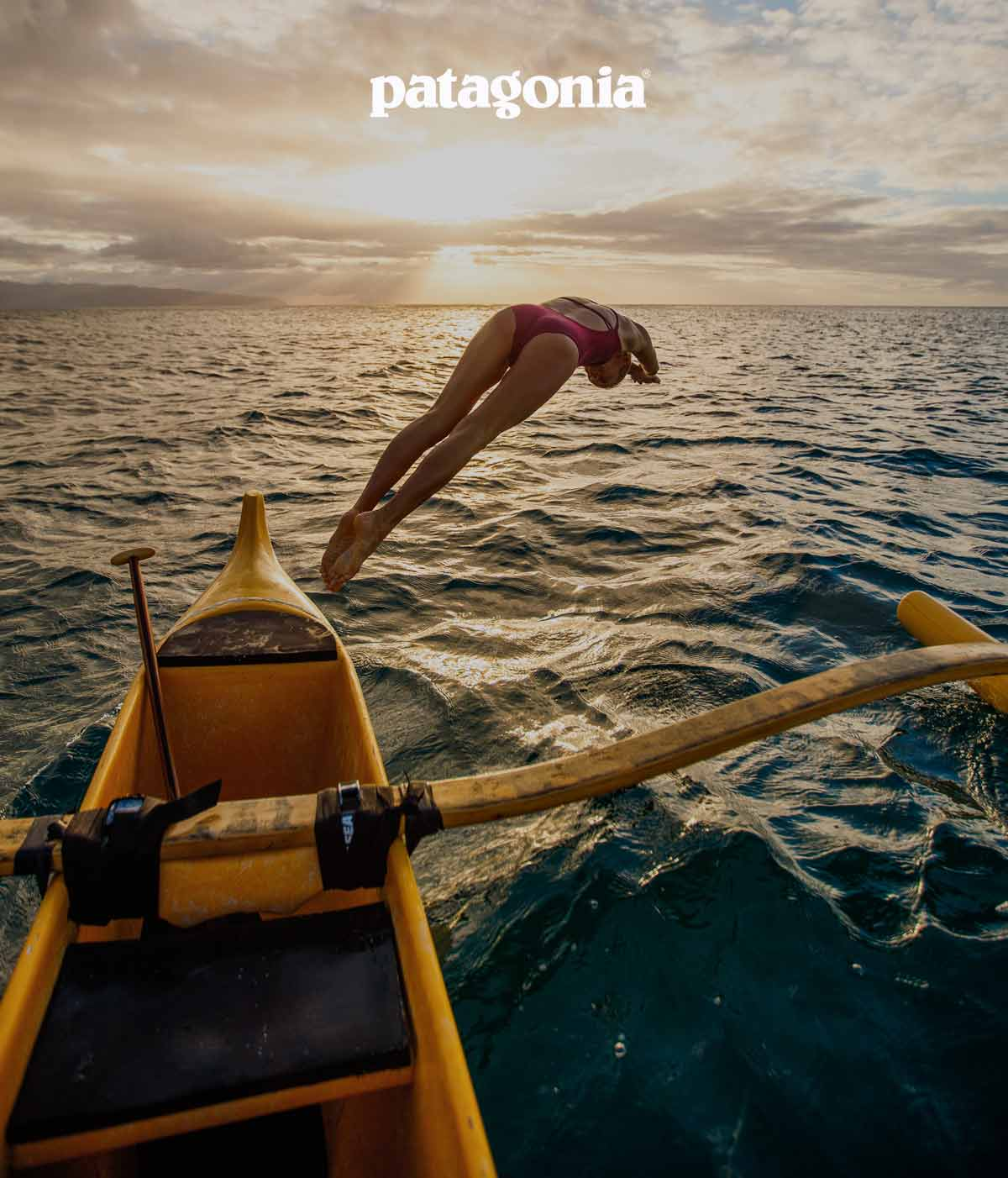 A person dives into the ocean from an outrigger canoe.